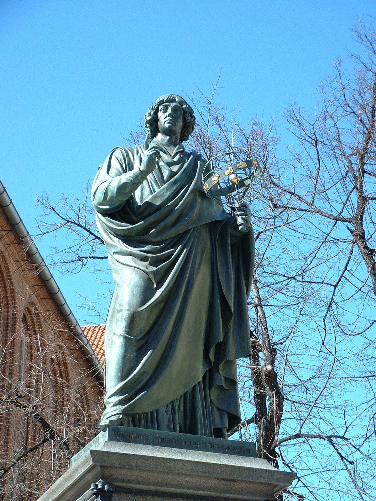 Pomnik Kopernika wystawiony przez niemiecką radę miasta Torunia w1853 r. PomnikKopernika wToruniu. Odsłonięty w1853 r., dzieło niemieckiego rzeźbiarza Friedricha Abrahama Ticka. Już wXVIII w. powstały pierwsze pomysły upamiętnienia astronoma wToruniu, ale wówczas rzeźba ufundowana przez księcia Jabłonowskiego nie spodobała się rajcom iumieszczono ją wKościele p.w. św. Jana. Ponownie do pomysłu wrócono wokresie Księstwa Warszawskiego zinicjatywy Stanisława Staszica, ale upadek państwa nie pozwolił zrealizować dzieła. Źródło: Christian Friedrich Tieck, Pomnik Kopernika wystawiony przez niemiecką radę miasta Torunia w1853 r., 2004, fotografia, licencja: CC BY-SA 3.0.