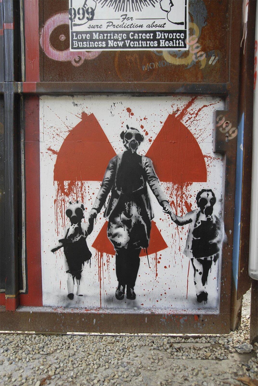 Zdjęcie przedstawia krytyczne wstosunku do energetyki atomowej graffiti na stalowym kontenerze. Na białym tle namalowany jest czerwoną farbą wiatraczek, symbol ostrzegawczy przed promieniowaniem radioaktywnym. Na tle tego znaku znajdują się czarnobiałe postacie kobiety zdwójką dzieci trzymanych za ręce. Cała trójka ma na twarzach maski przeciwgazowe.