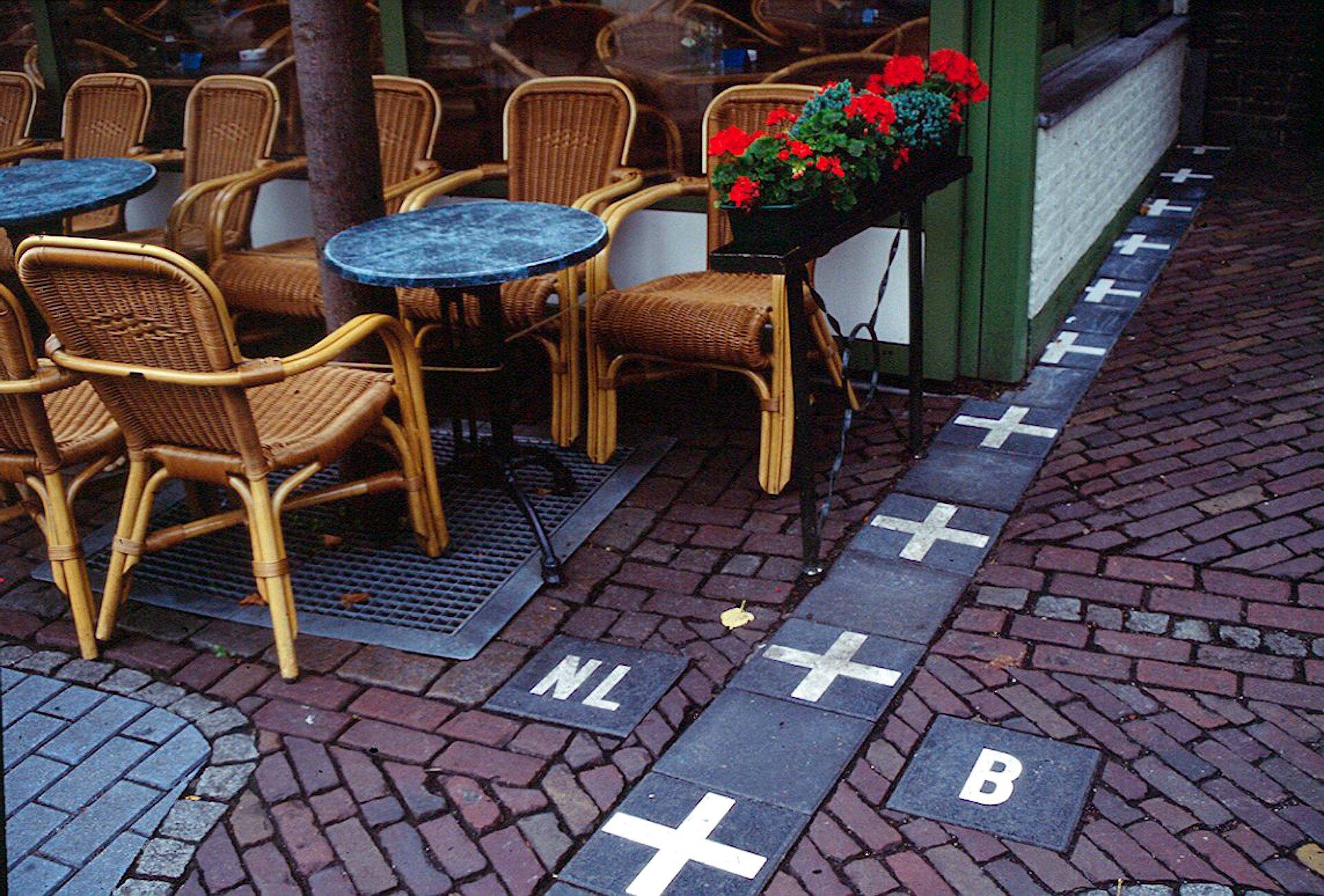 Zdjęcie przedstawia kawiarnię znajdującą się na granicy Holandii iBelgii. Na dole zdjęcia chodnik zczerwonej cegły. Od dolnej krawędzi zdjęcia poprowadzona jest granica składająca zczarnych kwadratowych płytek. Płytki ułożone wlinii, wzdłuż kawiarni. Linia płytek biegnie wprawo, zanika wgłębi zdjęcia. Białe krzyżyki na co drugiej czarnej płytce linii granicznej. Wdole zdjęcia, po lewej iprawej stronie pojedyncze czarne kwadratowe płytki. Na powierzchni płytek litery wskazujące państwa. Na lewo litery en el, Holandia, na prawo litera be, Belgia. Na lewo od linii granicznej, wiklinowe krzesła ustawione wrzędzie po obu stronach okrągłych stolików.