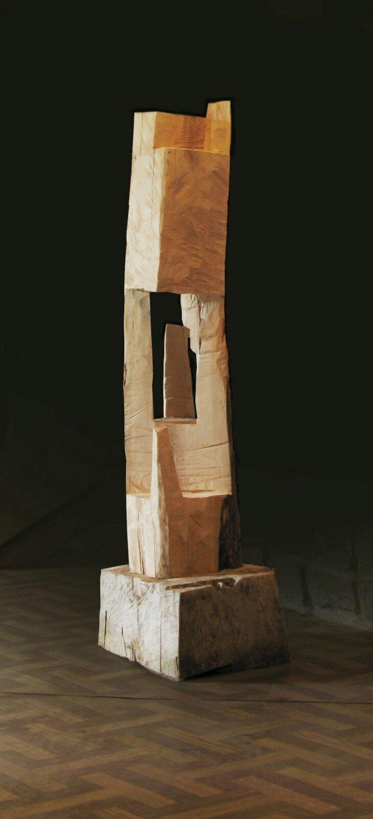 """Ilustracja przedstawia rzeźbę Krzysztofa Mazura """"Kapliczka przełamana"""". Jest to drewniany, ciosany pień drzewa ukształtowany wbryłę zbliżoną do prostopadłościanu, usytuowany na podstawie. Wśrodku pień jest wydrążony. Wprześwicie oraz na zewnątrz znajdują się pozostawione, niewycięte, pionowe fragmenty drewna."""