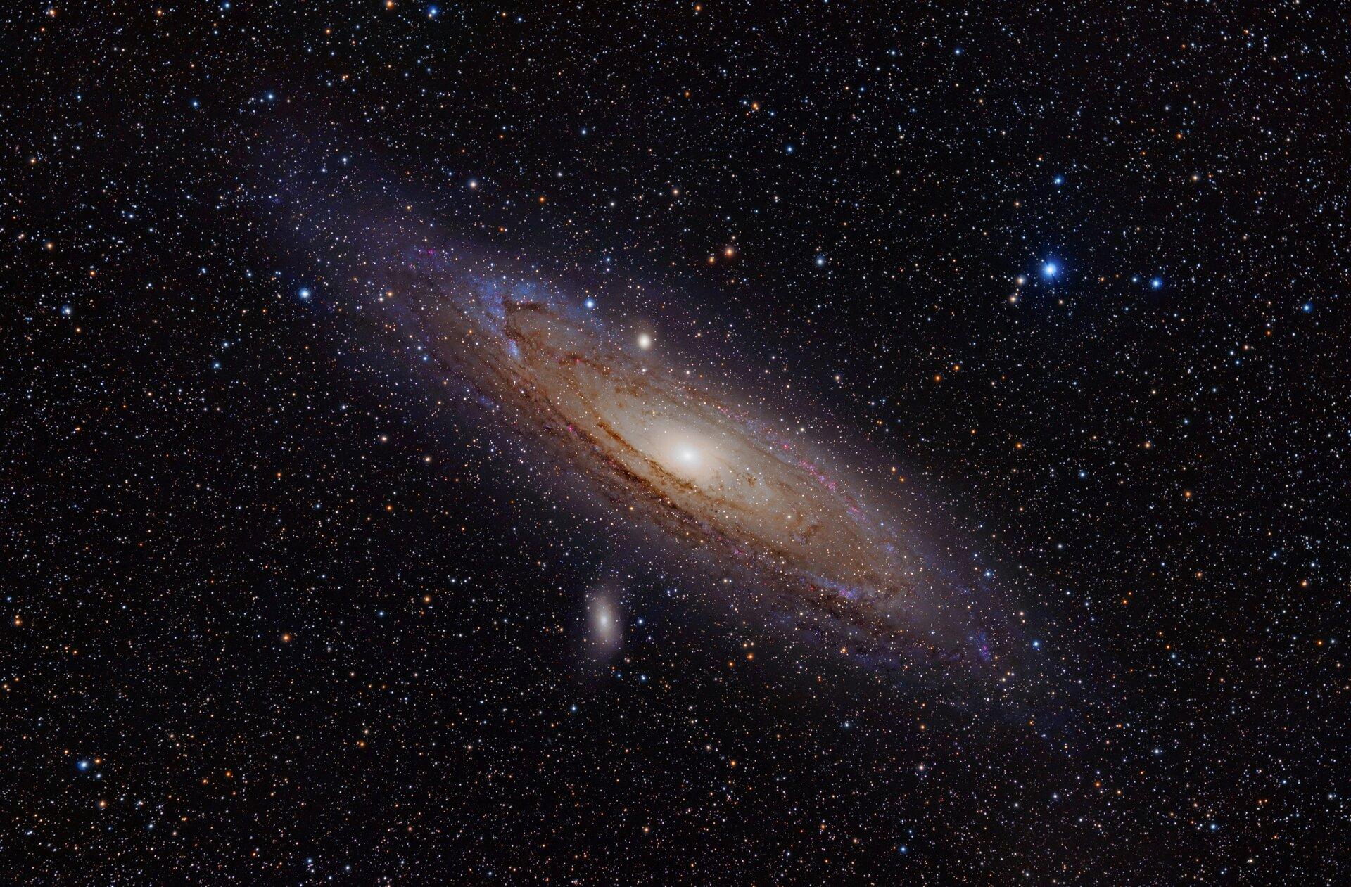 Zdjęcie przedstawia wielką galaktykę wgwiazdozbiorze Andromedy – spiralną zpoprzeczką.