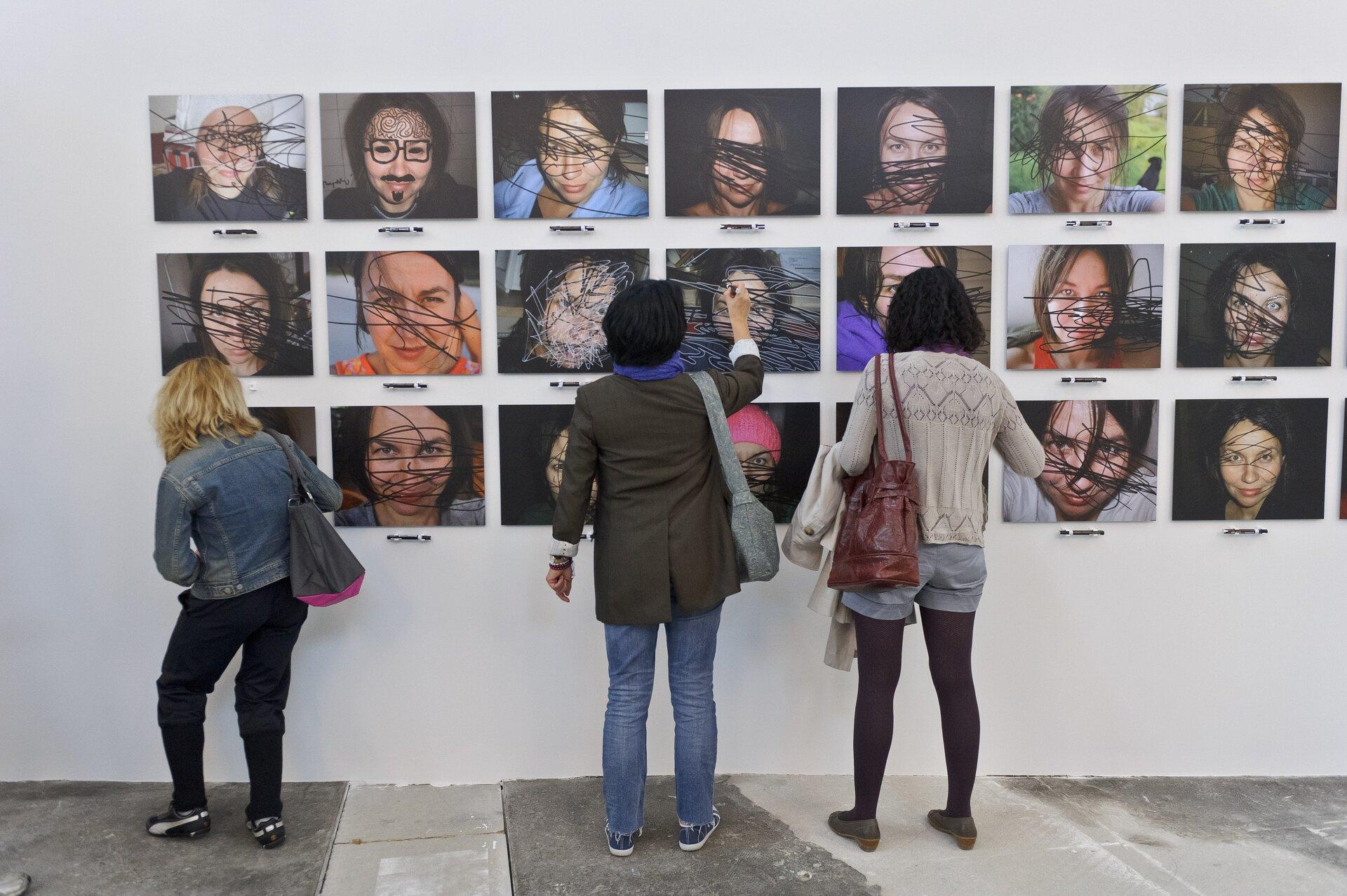"""Ilustracja przedstawiająca ludzi oglądających instalację artystyczną Elżbiety Jabłońskiej pt. """"Zamaż mnie""""."""