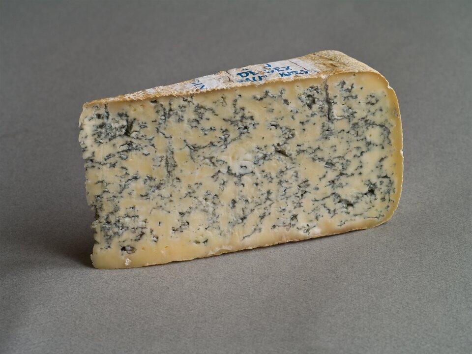 Fotografia przedstawia na szarym tle trójkątny wycinek sera pleśniowego. Ser jest żółtawy, zgrubszą skórką. Wewnątrz ser jest przerośnięty ciemnymi niteczkami pleśni.