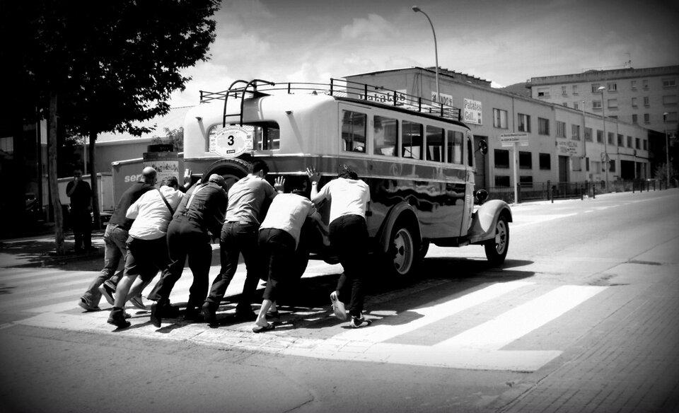 Czarno białe zdjęcie przedstawiające sześciu mężczyzn przepychających stary autobus ulicami małego miasteczka. Na budynkach wgłębi kadru widoczne są hiszpańskojęzyczne napisy.