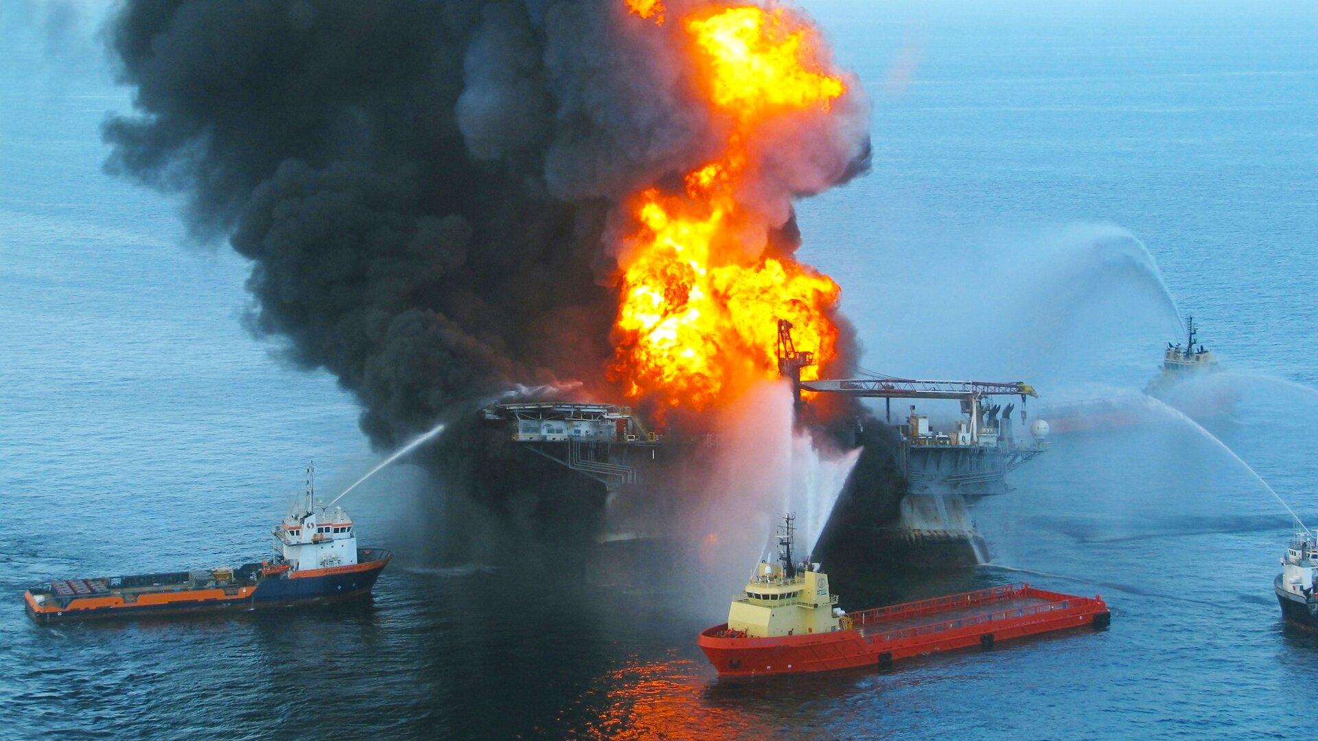 Zdjęcie przedstawia akcję gaszenia pożaru statku na morzu. Uczestniczą wniej cztery łodzie ratownicze, otaczające zczterech stron statek, na którym rozprzestrzenił się pożar. Płonie ogień, który widać na pewno zdużej odległości. Widać również ogromną chmurę dymu. Statek stoi na środku morza. Jest pochmurny dzień.