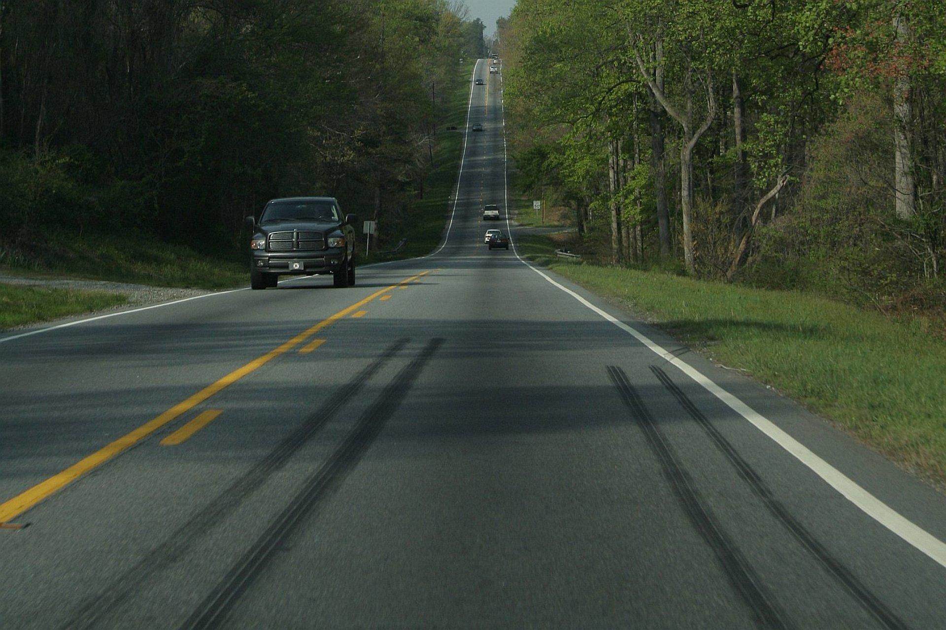 Zdjęcie przedstawia drogę zjadącymi samochodami zwysokim wzniesieniem wtle, aparat znajduje się nisko nad asfaltem. Na pierwszym planie na asfalcie widać ślady po bardzo ostrym hamowaniu.