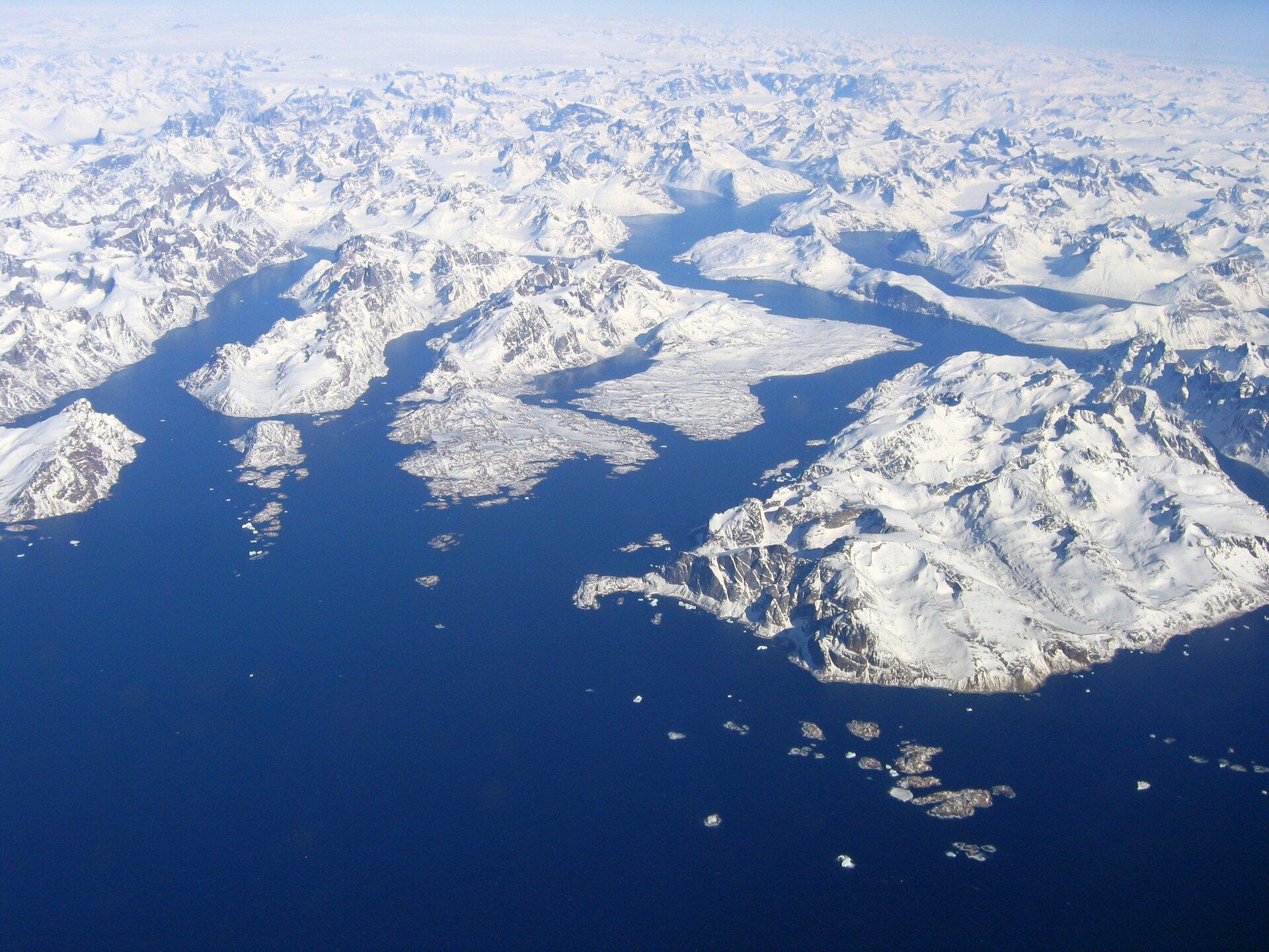 Fotografia prezentuje krajobraz strefy okołobiegunowej. Fotografia wykonana zgóry przedstawia rozciągające się po horyzont, białe wysokie góry lodowe na morzu.