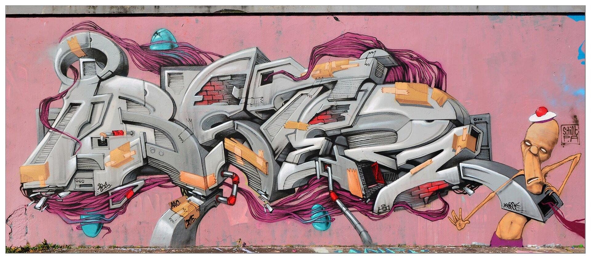 Zdjęcie przedstawia graffiti namalowane na różowej ścianie. Graffiti ukazuje szary napis wzbogacony innymi elementami graficznymi, zprawej strony znajduje się postać łysego, półnagiego mężczyzny zberetem na głowie.