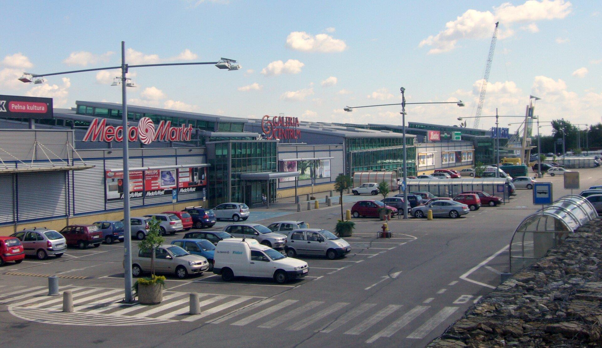 Na zdjęciu rozległa galeria handlowa zdużym parkingiem.