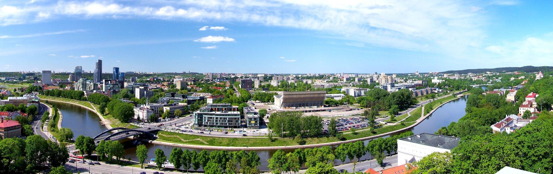 Na pierwszym planie rzeka, aza nią szeroka panorama nowoczesnego, dużego miasta. Zprawej stronie grupa wieżowców górująca nad reszta miasta.