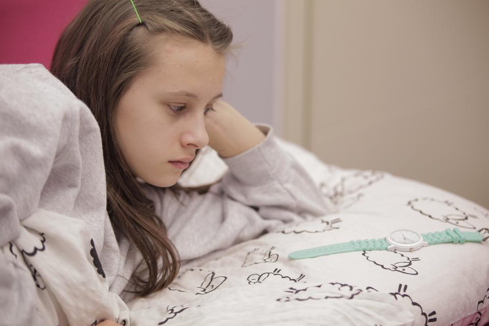 Fotografia przedstawia kilkunastoletnią dziewczynkę leżącą włóżku, wpościeli. Dziewczynka, leżąc na lewym boku ipodpierając głowę lewą ręką, spogląda na leżący na poduszce zegarek naręczny.