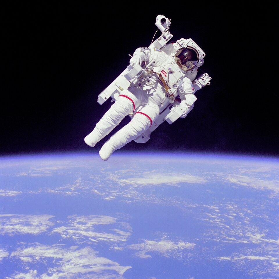 Na fotografii astronauta wbiałym kombinezonie unoszący się swobodnie wprzestrzeni kosmicznej. Sylwetka astronauty pochylona zpowodu nieważkości wkosmosie. Pod astronautą widoczna powierzchnia niebieskiej planety.