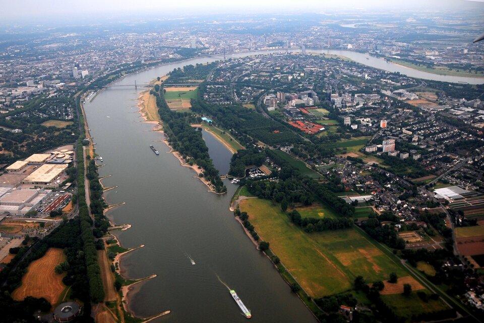 Na zdjęciu rzeka płynąca po równinnym terenie. Zabudowa mieszkaniowa iprzemysłowa.