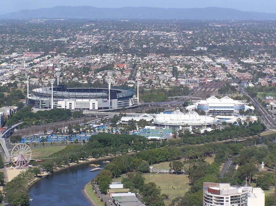 Na ilustracji gęsta, zwarta, niska zabudowa miejska. Na pierwszym planie duży kompleks obiektów sportowych położony nad rzeką.