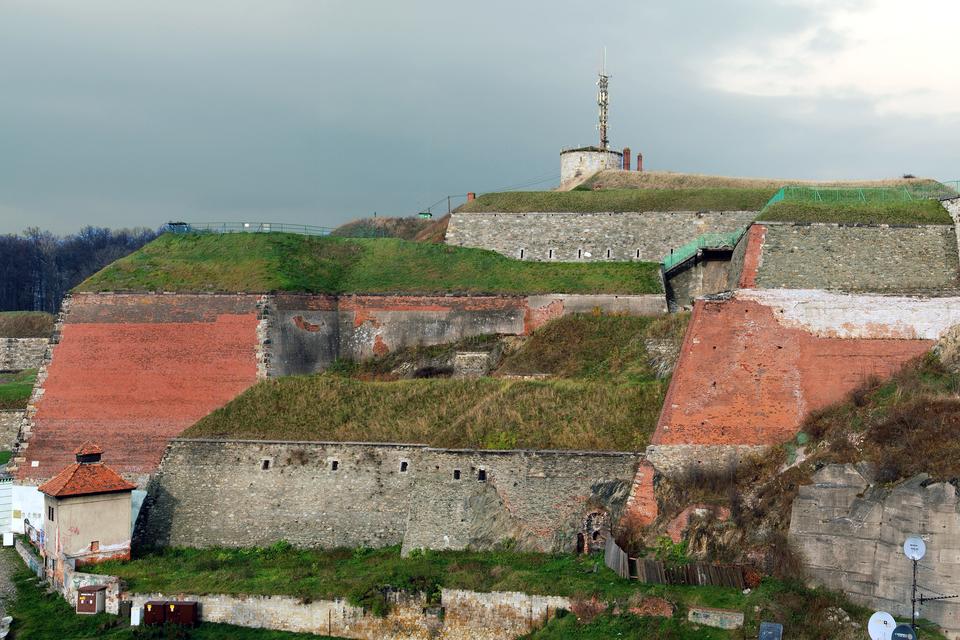 Fotografia prezentuje wysokie mury obronne twierdzy porośnięte trawą.