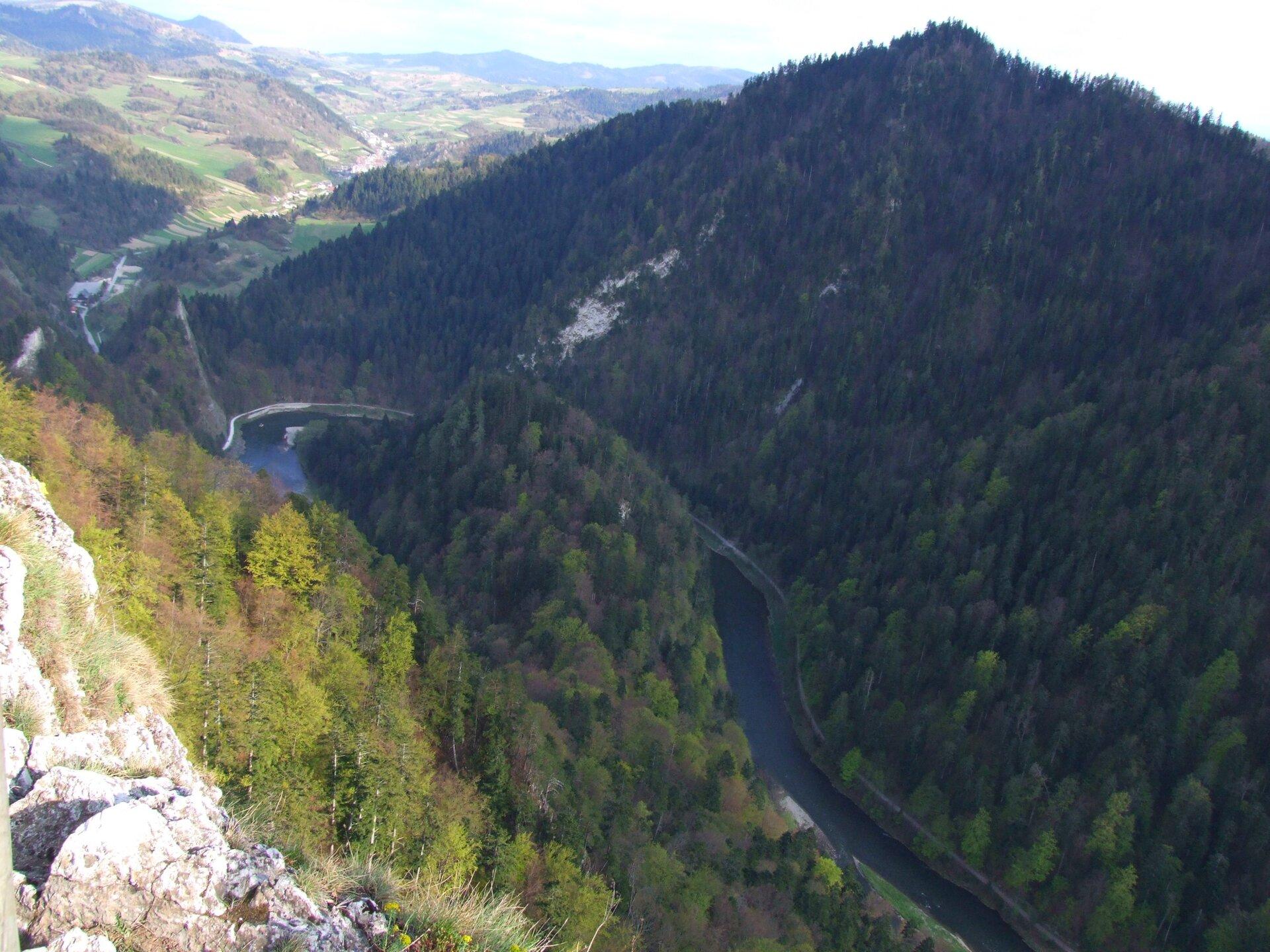 Na zdjęciu lotniczym kręta rzeka płynąca pomiędzy wysokimi wzniesieniami. Stoki gór porośnięte lasem.