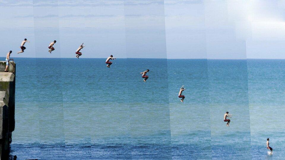 Ilustracja przedstawia kolaż utworzony zośmiu zdjęć przedstawiających młodego mężczyznę skaczącego do morza zbetonowego kilkumetrowego nabrzeża. Pionowe wycinki zdjęć ułożone zostały obok siebie ręcznie wtaki sposób, że linie złączeń są wyraźnie widoczne, alinia horyzontu nie jest do końca jednolita. Kolaż przedstawia kolejne fazy skoku: wybicie, osiągnięcie wysokości maksymalnej, spadek oraz zetknięcie nóg skoczka zpowierzchnią wody.