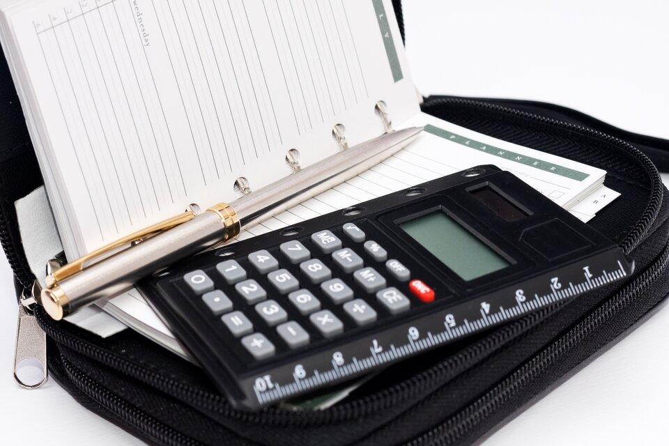 Fotografia przedstawia kalendarz wformie książeczki zwany terminarzem. Terminarz jest umieszczony wewnątrz etui zapinanego na zamek. Wwyposażeniu etui znajduje się także długopis oraz kalkulator elektroniczny.