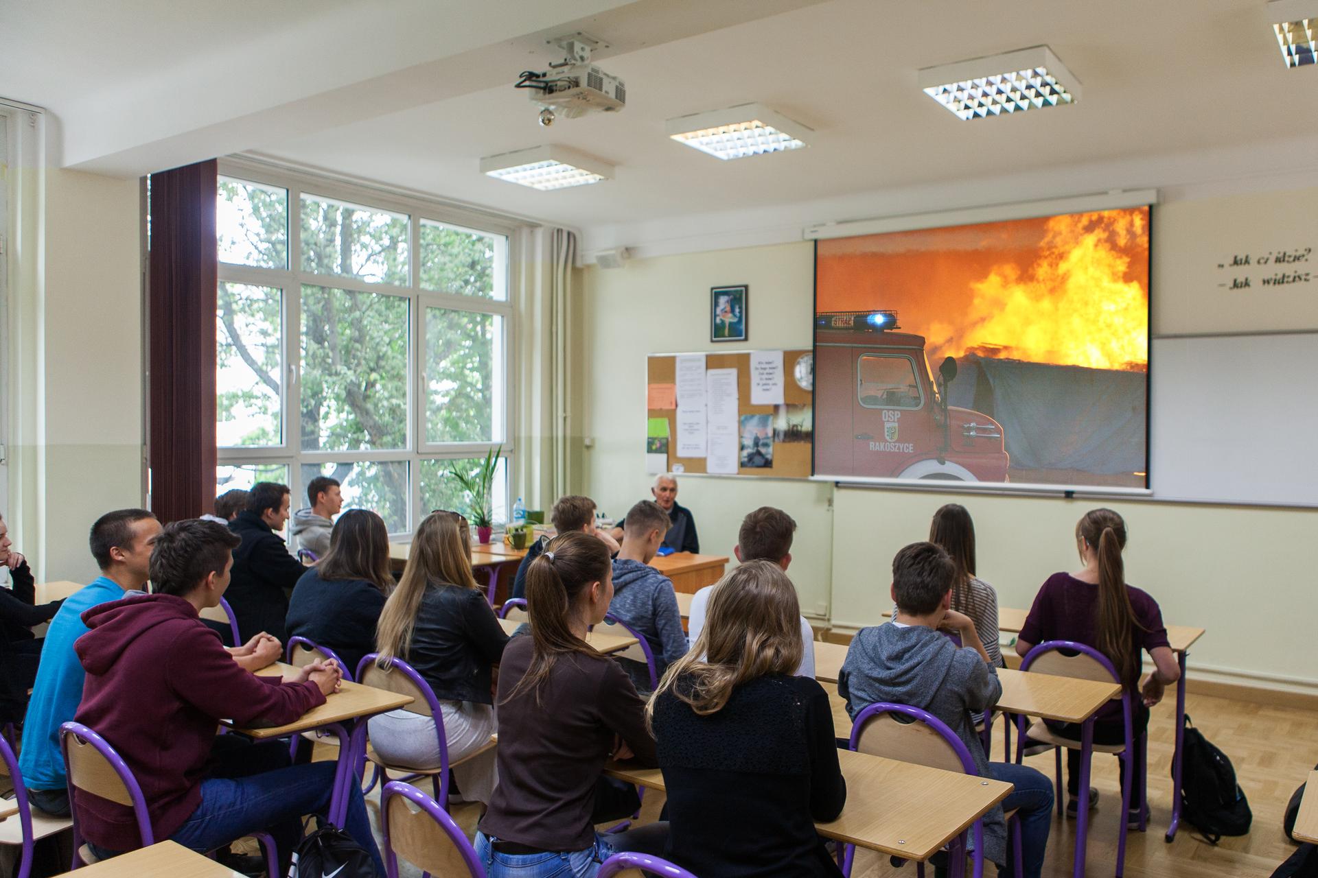 Kolorowe zdjęcie klasy lekcyjnej. Grupa uczniów siedzi wławkach tyłem do obserwatora zdjęcia, przodem do tablicy. Na ścianie, obok tablicy, rozciągnięty ekran. Na ekranie fragment filmu dotyczący ochrony przeciwpożarowej. Film przedstawia straż pożarną gaszącą pożar. Nauczyciel siedzi za biurkiem, wlewym rogu klasy.