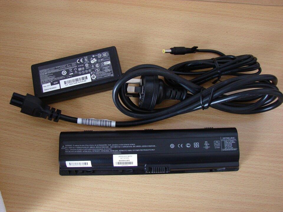 Zdjęcie przedstawia zasilacz do komputera przenośnego leżący na blacie biurka wraz okablowaniem iakumulatorem do notebooka. Ztabliczki znamionowej zasilacza można odczytać, że parametry prądu na wyjściu to 18,5 wolta i3,5 ampera.