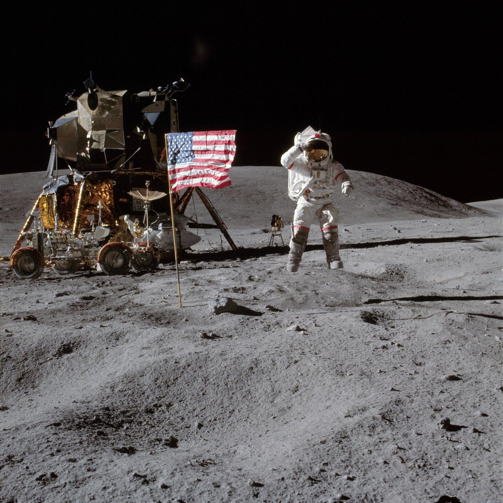 Zdjęcie przedstawia powierzchnię Księżyca. Na pierwszym planie pofałdowany teren pokryty szarym pyłem. Na środku pojazd kosmiczny oraz kosmonauta. Kosmonauta wbiałym kombinezonie, dużych ciężkich butach oraz kasku zzaciemnioną szybką. Amerykańska flaga na dwumetrowym drzewcu wetknięta wpowierzchnię Księżyca. Górny dłuższy bok flagi jest usztywniony poprzeczką, żeby wyglądała na powiewającą na wietrze. Skierowana jest wprawą stronę. Przestrzeń nad powierzchnią Księżyca czarna.