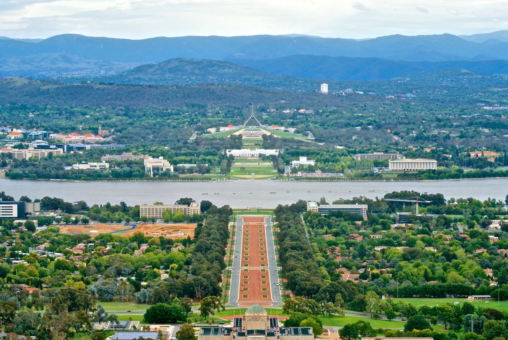 Na zdjęciu widok na miasto. Widok zgóry na szeroką aleję ikompleks budynków. Dużo terenów zielonych. Pośrodku zbiornik wodny. Wtle wysokie góry.