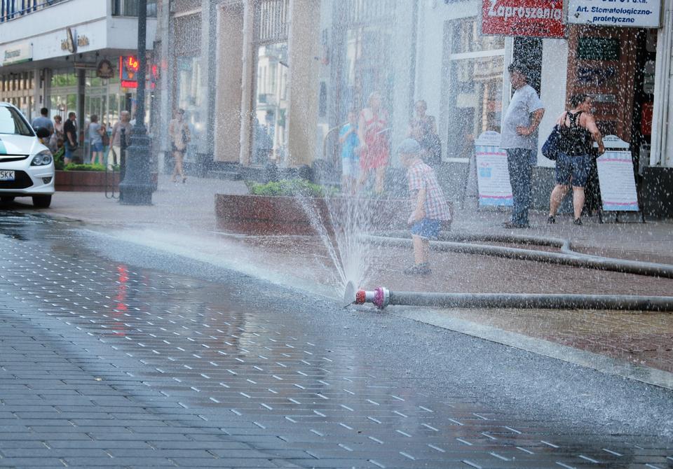Zdjęcie wkształcie poziomego prostokąta. Dzień. Na pierwszym planie ulica ichodnik wcentrum miasta pokryte kostką brukową. Po prawej wąż strażacki. Wąż rozciągnięty poprzecznie przez chodnik aż do krawężnika. Koniec węża zakończony zaworem. Woda tryskająca pod dużym ciśnieniem, tworzy strumień wkształcie wachlarza. Jest to tak zwana kurtyna wodna. Za strumieniem wody mały chłopiec wczapce. Za chłopcem przechodnie. Osoby ubrane wlekkie letnie ubrania. Wtle sklepy, latarnie ikwietniki.