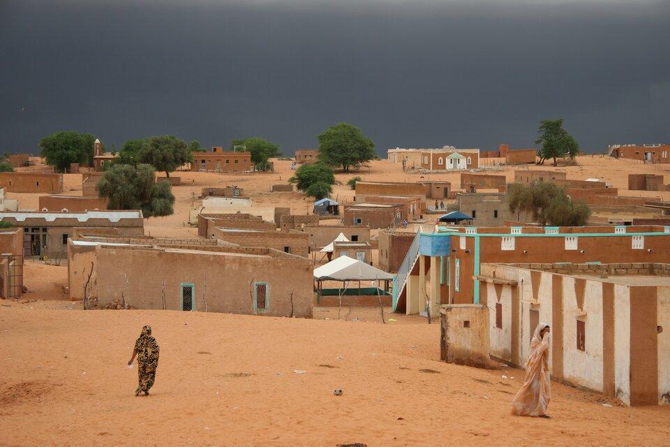 Na zdjęciu teren zabudowany, parterowe domki opłaskich dachach, pojedyncze drzewa, dwie kobiety.