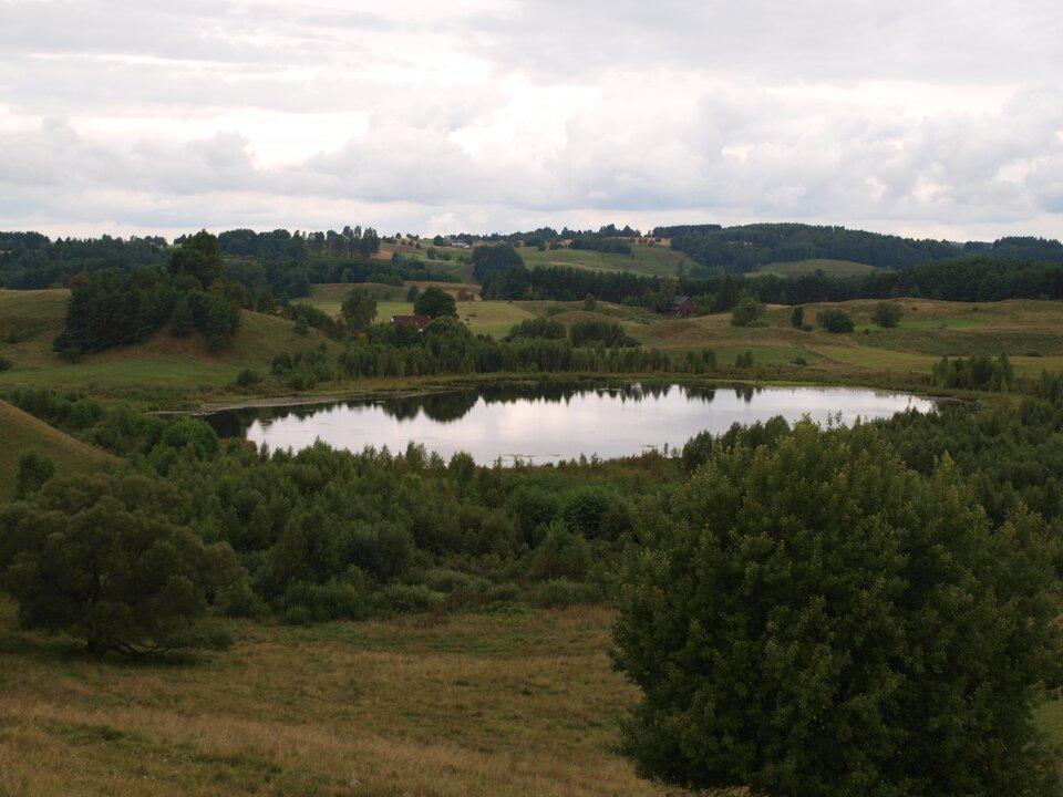 Na zdjęciu niewielkie okrągłe jeziorko wlekko pofałdowanym terenie porośniętym drzewami.