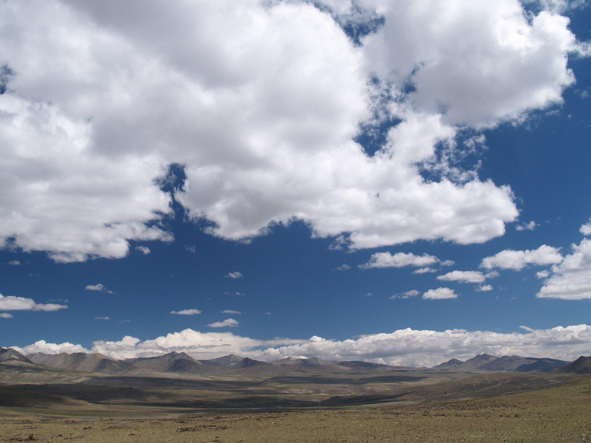Fotografia przedstawia pofałdowany krajobraz Wyżyny Tybetańskiej. Na niebie białe, rozbudowane chmury kłębiaste.