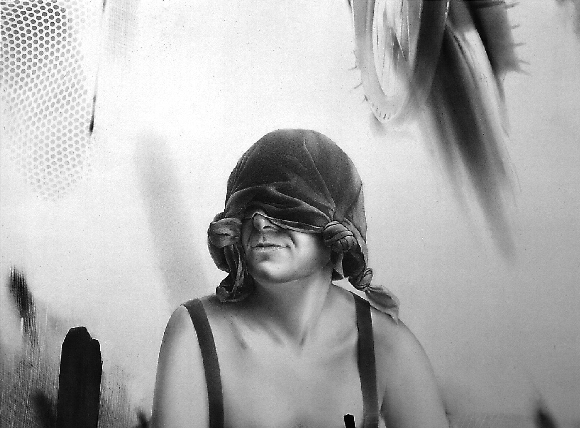 """Ilustracja przedstawia czarno-biały rysunek """"Portret M."""" autorstwa Jędrzego Gołasia. Artysta, przy pomocy delikatnego cieniowania narysowała portret mężczyzny znasuniętą na oczy, zawiązaną na czterech rogach, ciemną tkaniną. Postać na nagie ramiona ma naciągnięte szelki. Tło stanowią plamy oróżnej strukturze inatężeniu: od delikatnych przetarć, poprzez frottage siatki aż po czarne, nakładane aplą plamy. Rysunek tchnie sielską atmosferą, mężczyzna sprawia wrażenie zrelaksowanego."""