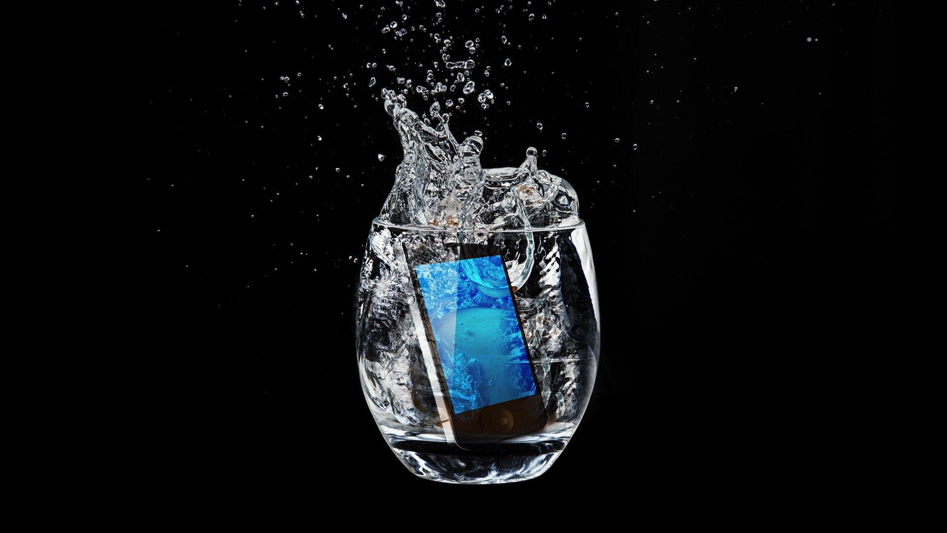 Zdjęcie przedstawia smartfona wrzuconego do szklanki zwodą.