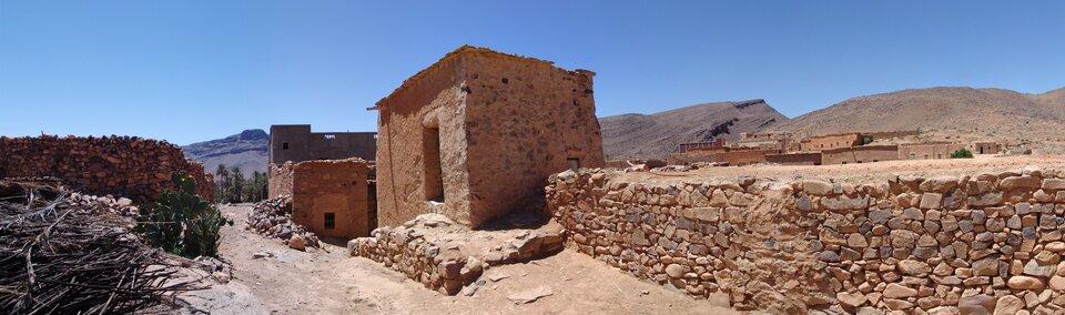 Fotografia prezentuje dom wraz zmurem zbudowany zkamieni pośród pustyni.