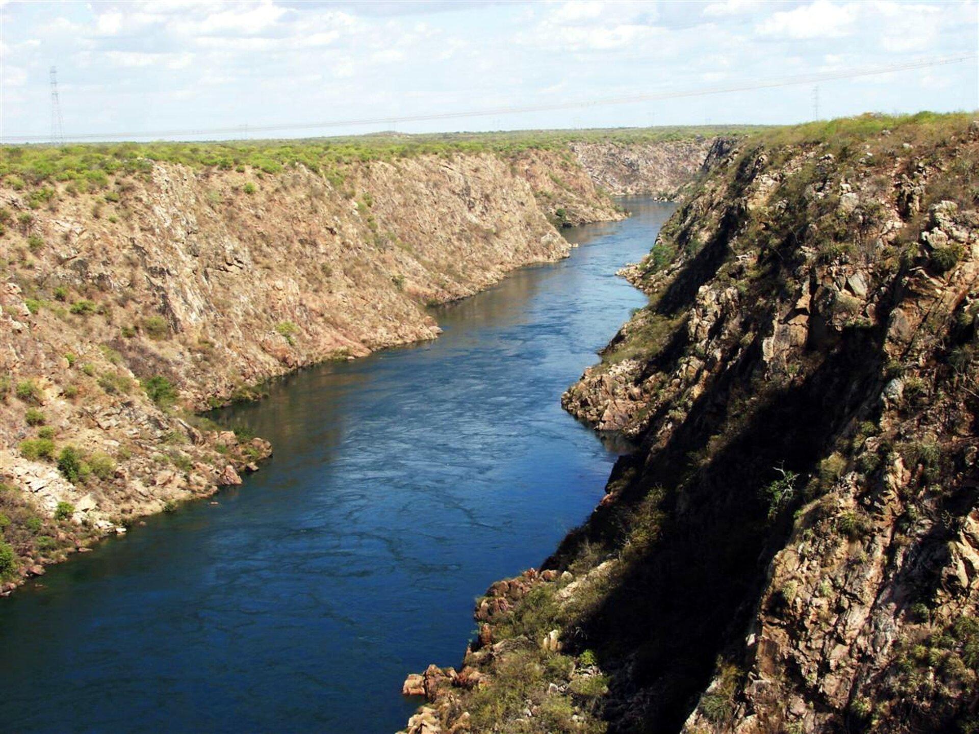 Na ilustracji rzeka płynąca wgłębokiej dolinie ostromych zboczach. Zbocza kamieniste, odsłonięte. Nurt rzeki wartki.