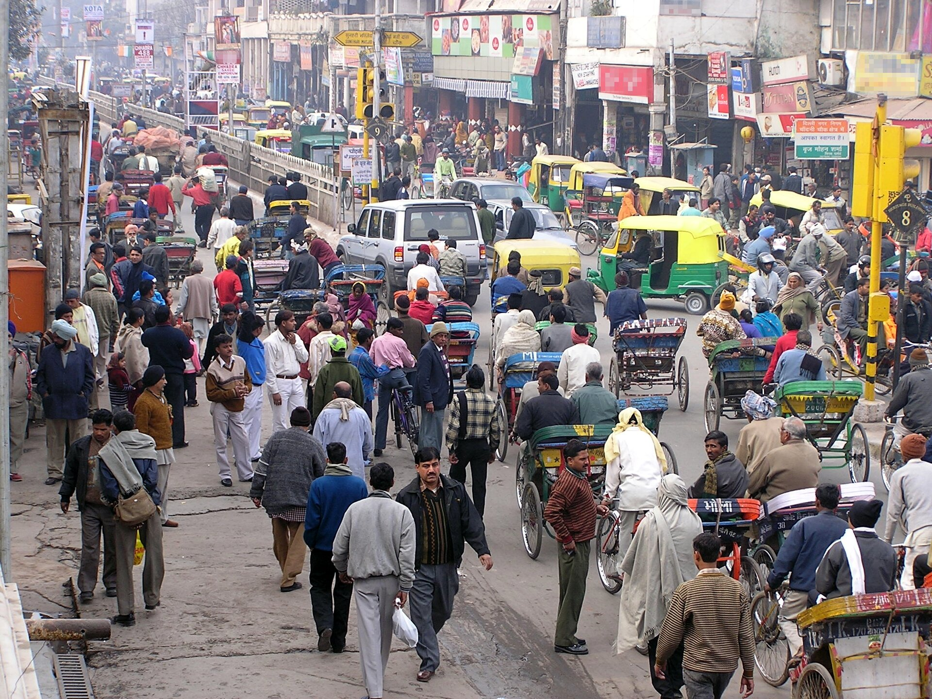 Na zdjęciu ulica wDelhi. Panuje duży tłok. Na chodnikach przechodnie, na ulicy samochody, riksze itakże przechodnie. Po prawej stronie ulicy widać zabudowę. Dużo szyldów.