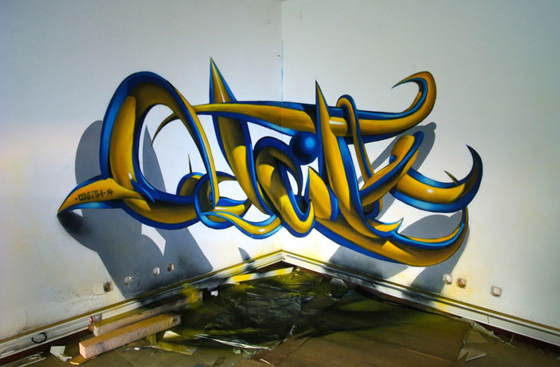 Ilustracja przedstawia graffiti Sergio Odeith'a. Ukazuje żółty napis zniebieskim konturem zamieszczony wrogu ściany wtaki sposób, że tworzy efekt trójwymiarowy. Na ścianie ipodłodze został namalowany cień napisu.