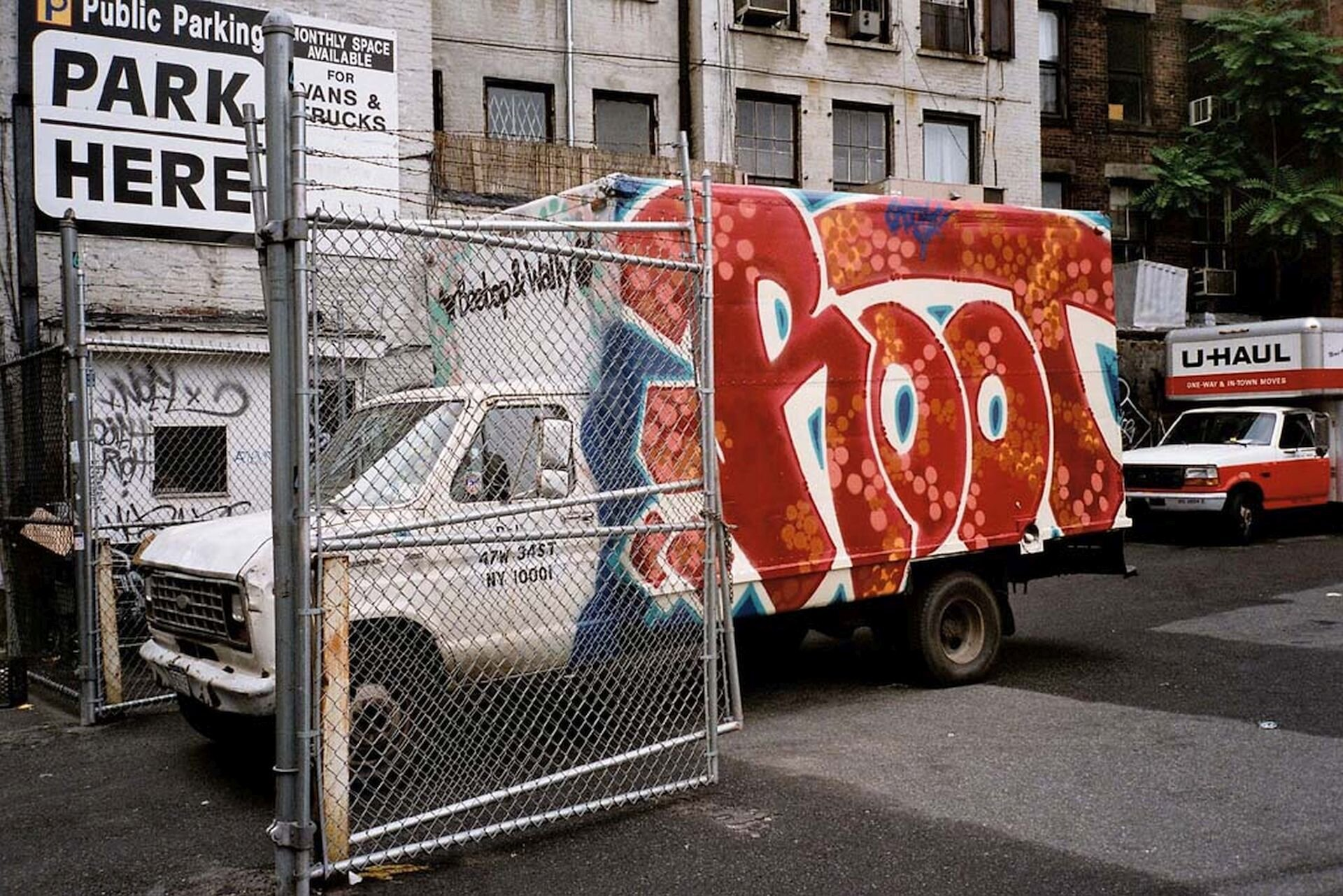 """Ilustracja przedstawia samochód dostawczy zgraffiti na bocznej ścianie. Jest to napis """"Root"""", wykonany wczerwonym kolorze, wróżowe iżółte kropki. Umieszczony jest na niebieskim tle. Na pierwszym planie jest otwarta brama."""