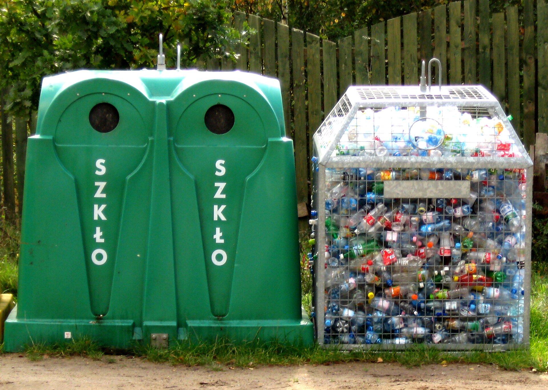 Fotografia przestawia dwa pojemniki do selektywnej zbiórki odpadów. Pojemniki stoją wwydzielonym miejscu przy ulicy. Zlewej duży zielony kontener zdwoma okrągłymi otworami ugóry. Pod nimi pionowo napisy SZKŁO. Obok siatkowy pojemnik na plastikowe opakowania. Na górze siatki ma okrągły otwór. Znajdują się wnim głównie butelki po napojach.
