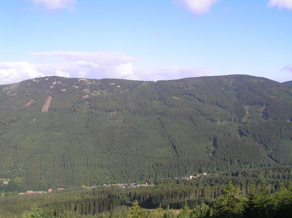 Na ilustracji pasmo górskie ołagodnych, zalesionych stokach. Po lewej nieco wyższy szczyt.