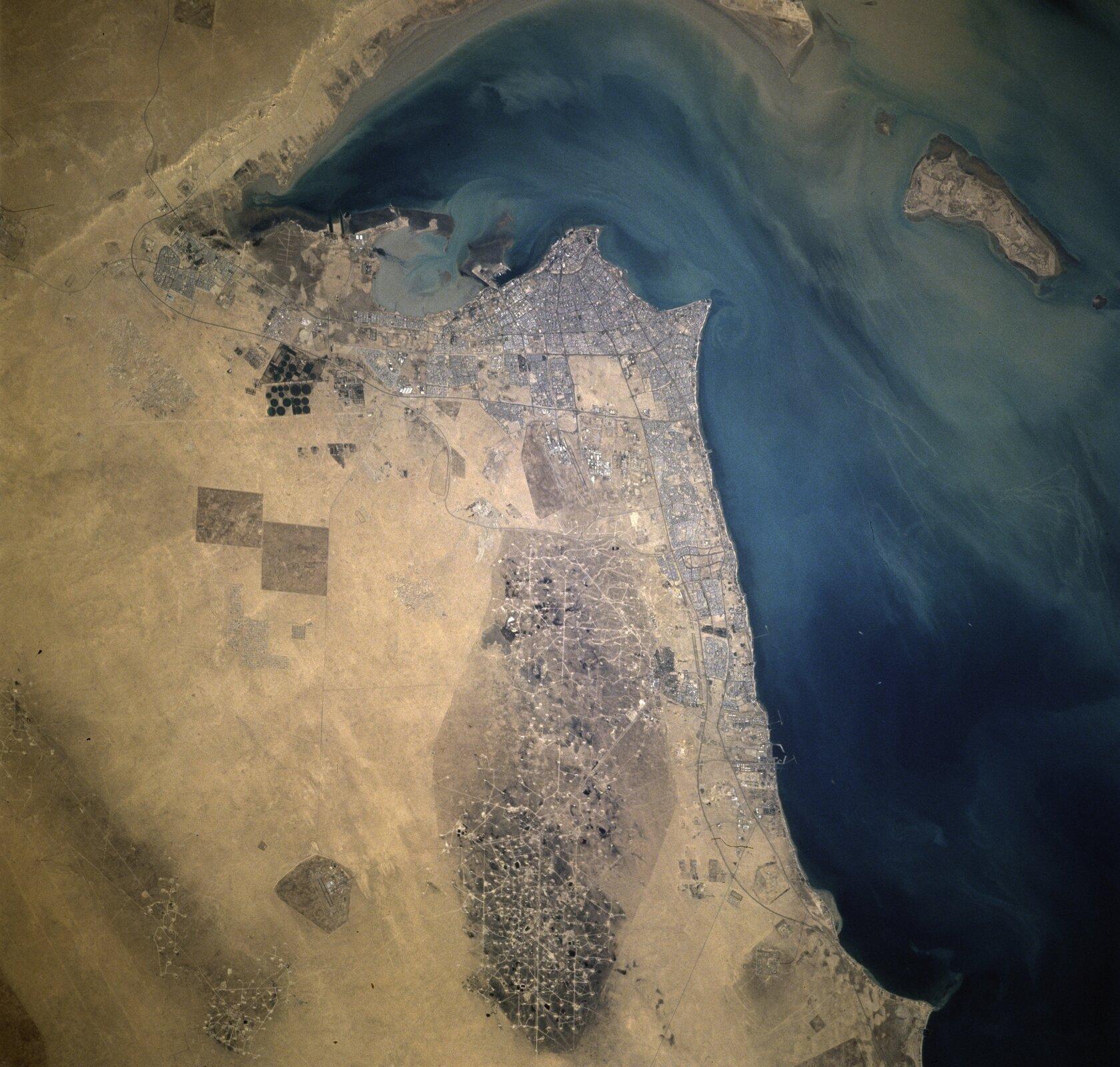 Na zdjęciu satelitarnym ląd położony nad morzem, gęsta zabudowa przy brzegu, dalej rozległe tereny pozbawione roślinności izabudowań, gdzieniegdzie ciemniejsze plamy.