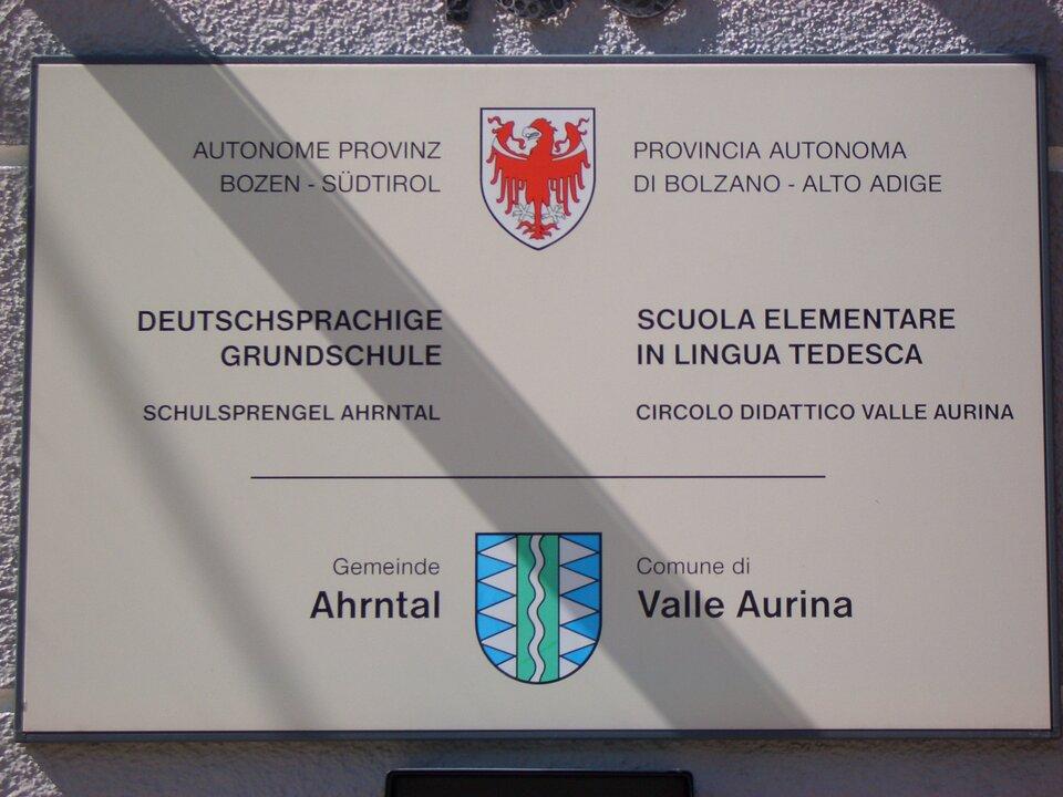Biała tablica znapisami wjęzyku włoskim iniemieckim. Dwa kolorowe herby, nazwy szkół inazwy miast.