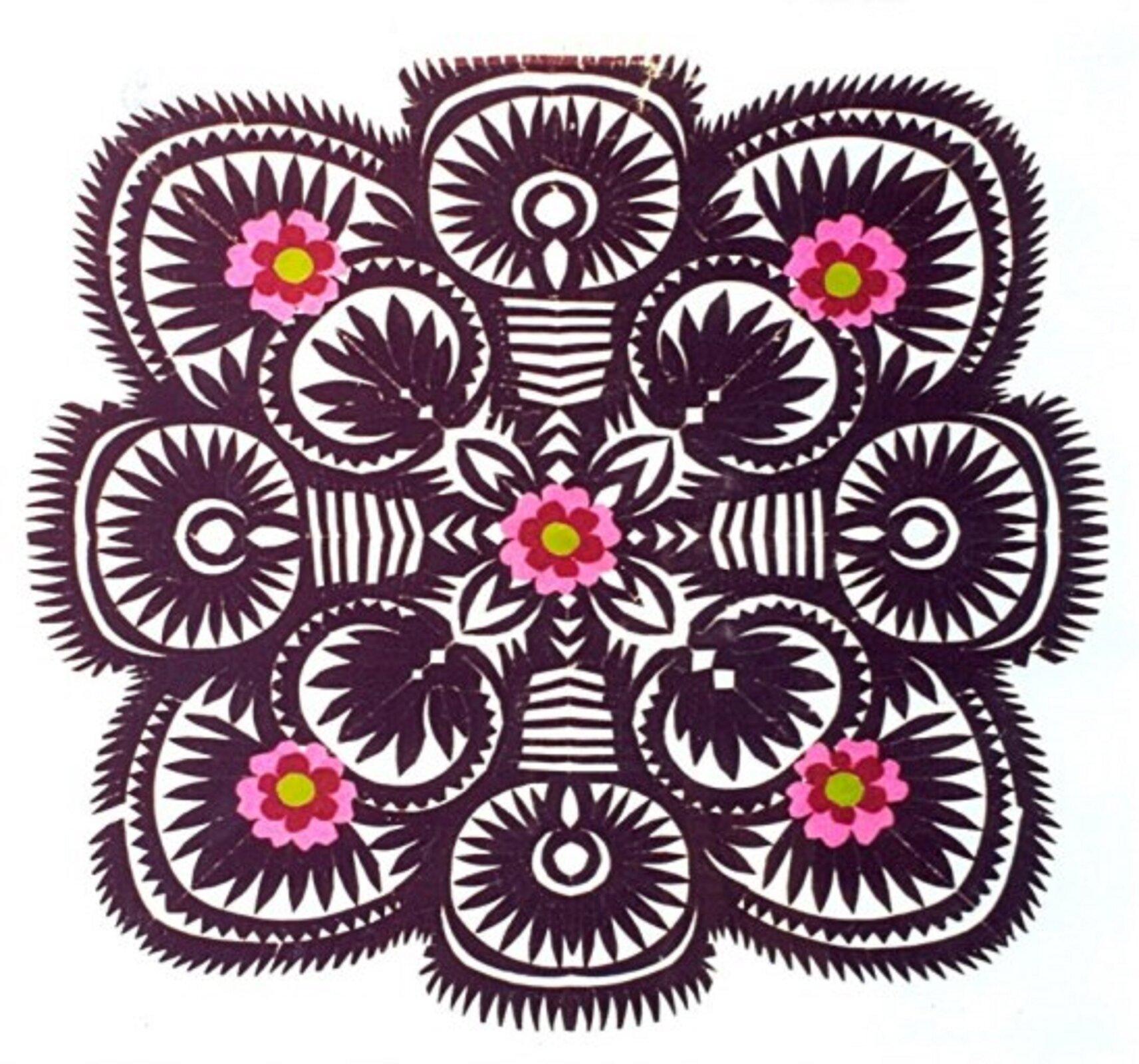 Ilustracja przedstawia sieradzki mazur. Jest to wzór wycinaki wkolorze ciemno-brązowym omotywie roślinnym. Składa się zwielu okrągłych lub półokrągłych części wśrodku których są kwiaty lub liście. Na wzorze wyróżnić można pięć kwiatów rozmieszczonych wrogach icentralnym punkcie, które są innego koloru niż całość. Płatki są różowo-czerwone, aśrodek żółty.