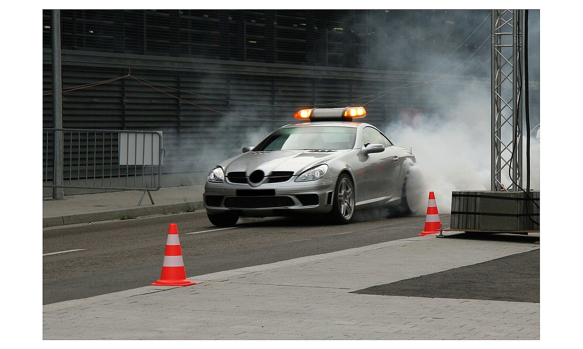 Zdjęcie przedstawia sportowy samochód. Samochód srebrnoszary. Znajduje się na asfaltowej drodze. Zokolic tylnych kół wydobywa się smuga dymu.