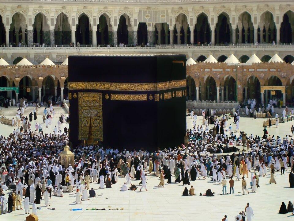 Na zdjęciu duża czarna budowla wkształcie prostopadłościanu ozdobiona złotymi ornamentami na środku placu. Dookoła dużo ludzi. Wtle dwa piętra arkad złukami.