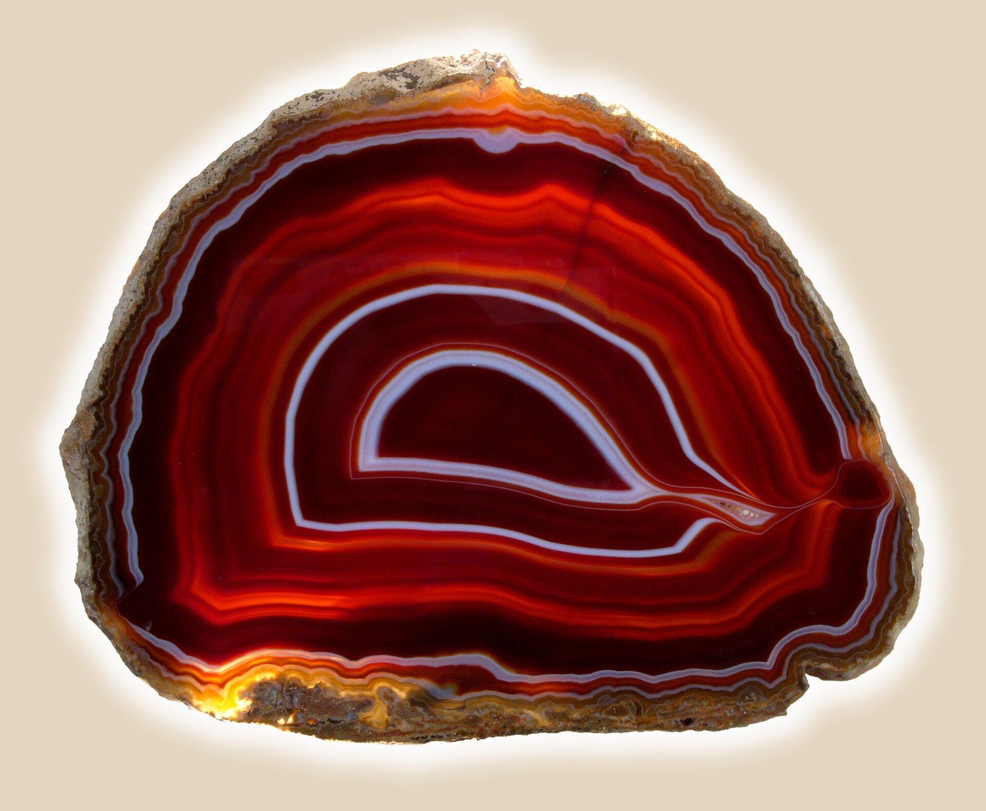Zdjęcie przedstawia agat wprzekroju owidocznych warstwach czerwonych, bordowych, ibiałych. Zewnętrzna warstwa kamienia żółtawa. Widoczne jest jedno epicentrum warstw, zprawej strony mocno rozciągnięte, aż do krawędzi kamienia.