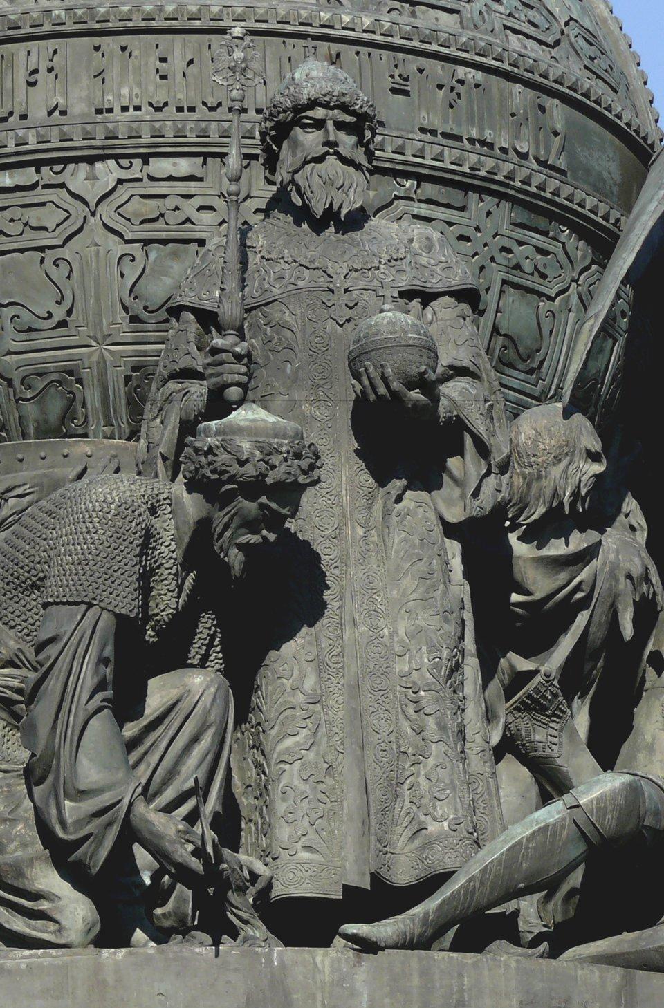 """Car Iwan III Srogi (1562-1505) na pomniku """"tysiąclecia Rosji"""" wNowogrodzie Wielkim wzniesionym w1862 r. Elementpomnika nazwany: """"Założenie jedynowładczego (samodzierżawnego) carstwa rosyjskiego 1491"""" – Iwan III, nazywany Srogim lub Wielkim, przedstawiony został wtradycyjnych szatach carskich ztzw. """"czapką Monomacha"""" (koronacyjne nakrycie głowy wielkich książąt moskiewskich, apóźniej carów); ustóp władcy leżą pokonani wbitwach Litwin irycerz zakonny ze złamanym mieczem. Na planie tylnym figura symbolizująca """"Sybiraka"""" – nowy cel ekspansji. Nazwa Carstwo Rosyjskie jest ahistoryczna dla postaci Iwana III, ponieważ dopiero w1547 r. odbyła się koronacja Iwana IV Groźnego na cara Wszechrusi (tytuł ten długo jeszcze nie był uznawany przez państwo polsko-litewskie). Źródło: Дар Ветер, Car Iwan III Srogi (1562-1505) na pomniku """"tysiąclecia Rosji"""" wNowogrodzie Wielkim wzniesionym w1862 r., 2010, fotografia, licencja: CC BY-SA 3.0."""