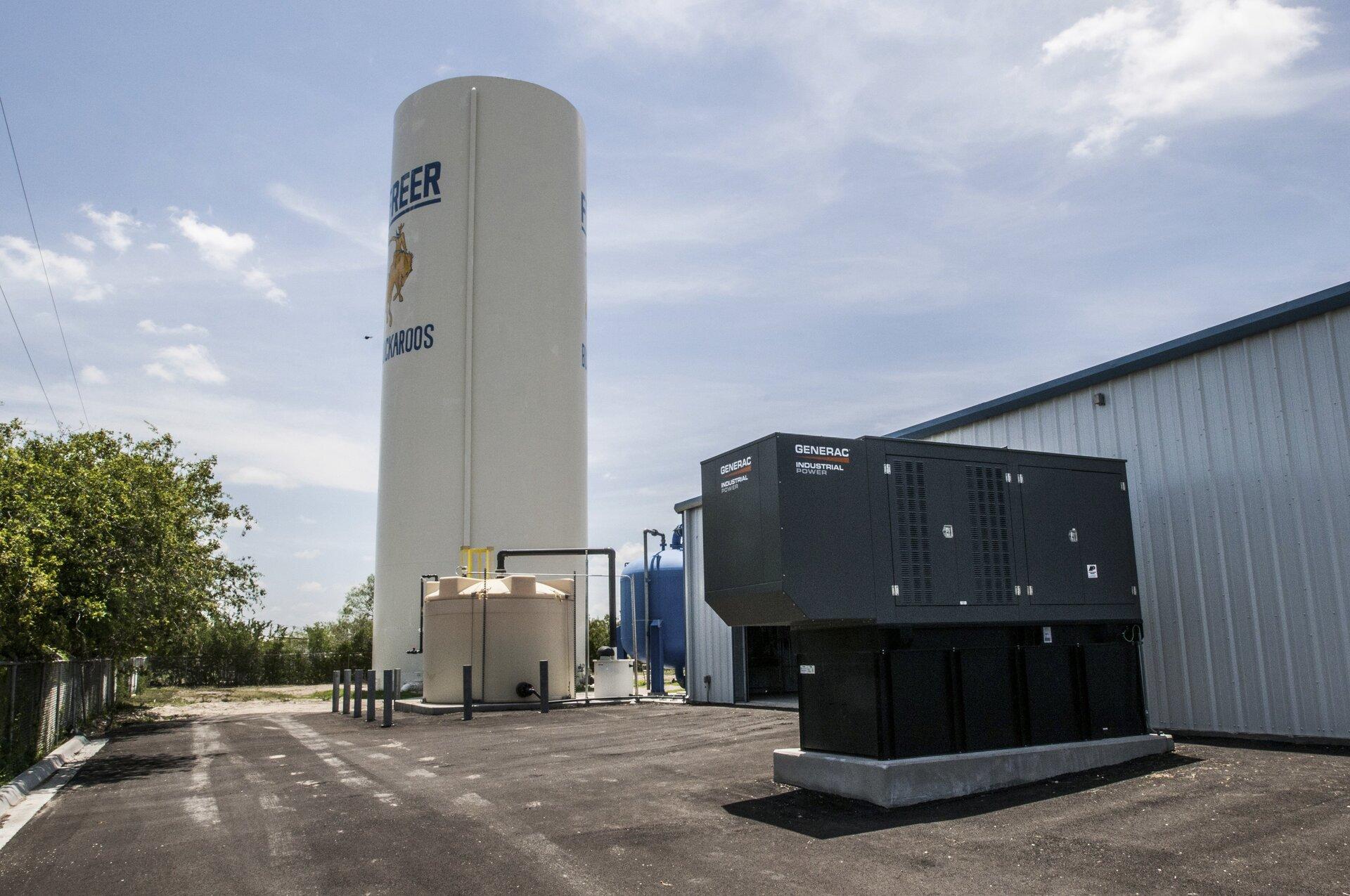Zdjęcie przedstawia instalację do neutralizowania arszeniku wwodzie czerpanej ze studni głębinowych. Teren otoczony drzewami, plac pokryty asfaltem. Po prawej stronie budynek kontenerowy zwjazdem dla ciężarówek icystern, wcentrum kadru wieża ciśnień oraz dwa mniejsze metalowe zbiorniki: jeden na wodę, adrugi na chlorowodór wykorzystywany jako regulator kwasowości.