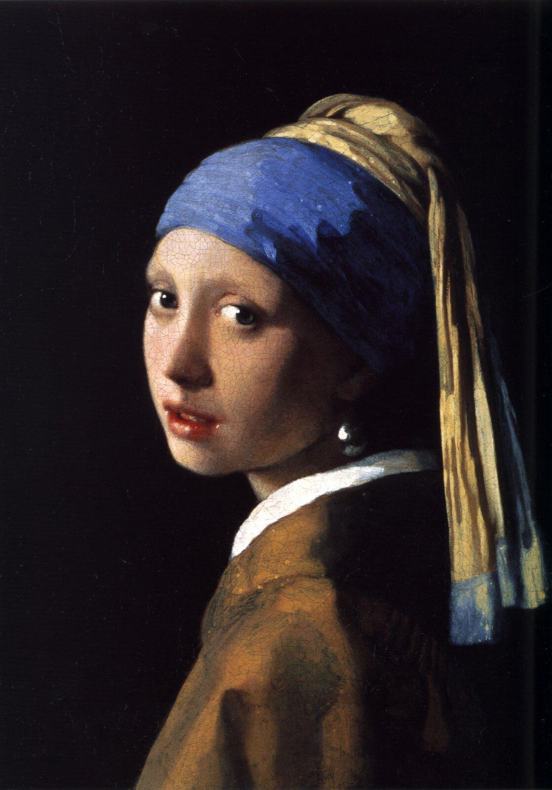 """Ilustracja przedstawia obraz olejny """"Dziewczyna zperłą"""" autorstwa Jana Vermeera. Dzieło ukazuje młodą dziewczynę, ubraną wbeżowo-żółtą suknię zbiałym kołnierzem oraz niebiesko-beżowy turban. Twarz stojącej bokiem postaci zwraca się wkierunku odbiorcy. Czerwone, dziewczęce usta są lekko uchylone. Wyraźnym akcentem obrazu jest duża perła wkolczyku dziewczyny, wktórej odbija się otoczenie. Ustawiona na ciemnym tle postać oświetlona jest miękkim światłem padającym zlewej strony. Kompozycja jest statyczna, co podkreśla nastrój wyciszenia ispokoju. Na obrazie dominują beże przełamane ultramaryną turbanu iczerwienią ust."""