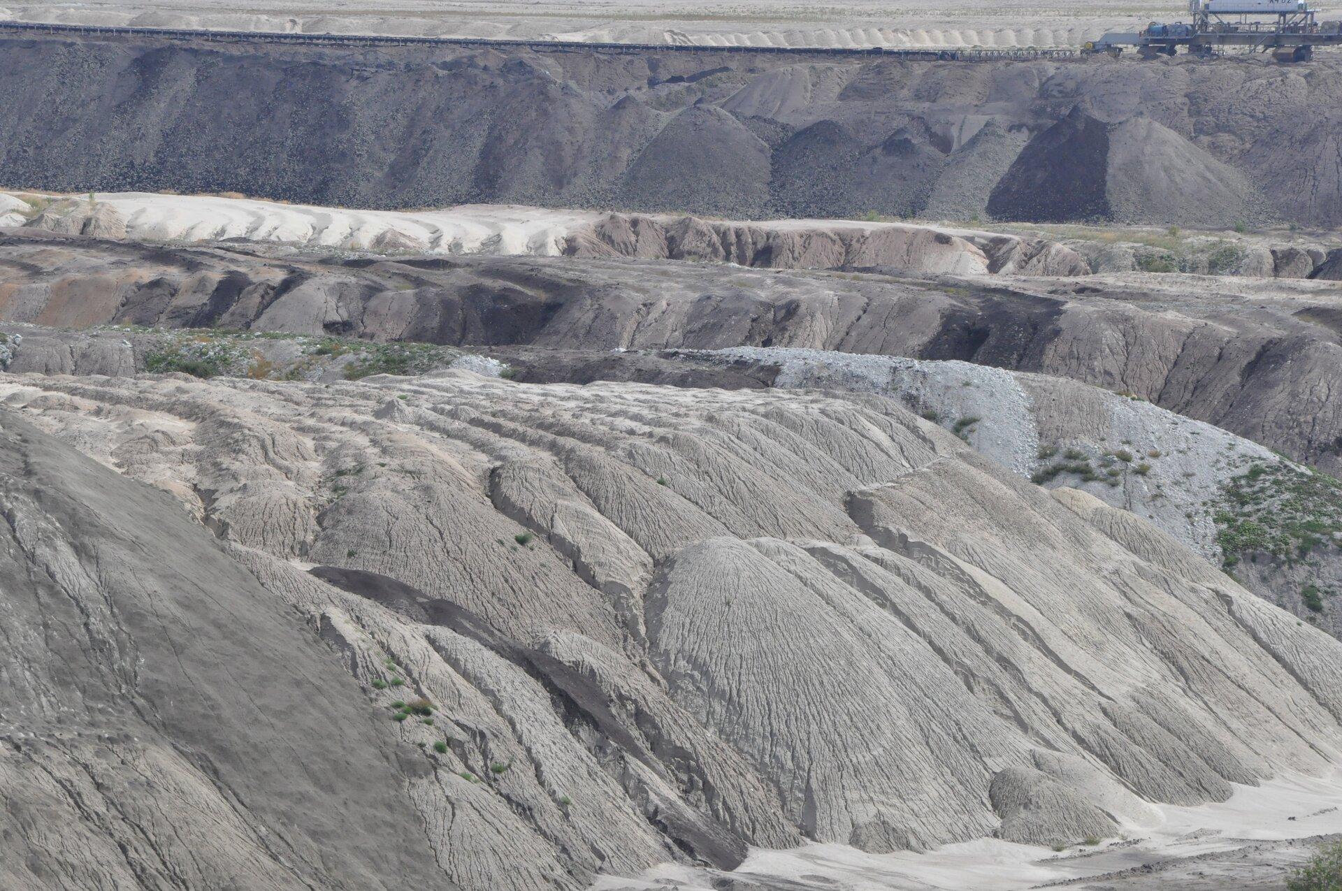 Fotografia prezentuje hałdę zbudowaną zusypanych odpadów, powstałych podczas wydobycia surowców.