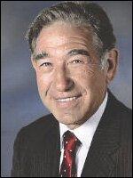 Fotografia przedstawia uśmiechniętego mężczyznę weleganckim garniturze.